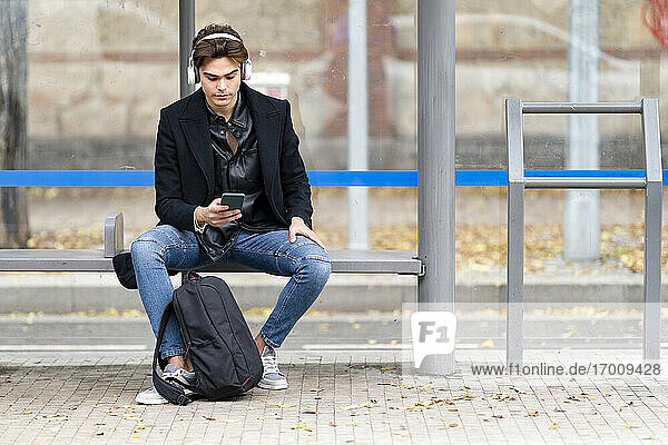 Handsome young man listening music while using smart phone sitting on bench at bus stop