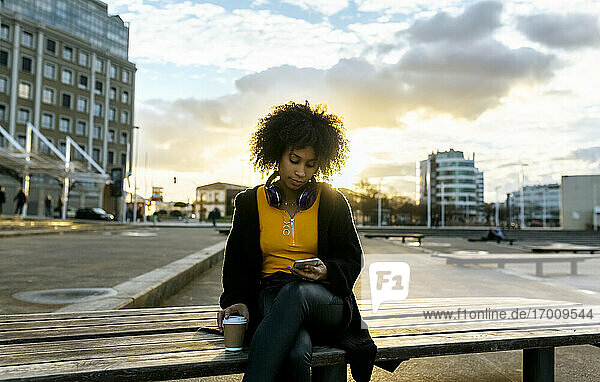 Young woman with afro hair using mobile phone while sitting on bench against sky in city