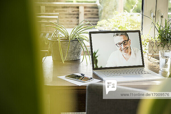 Smiling man photograph on laptop at home