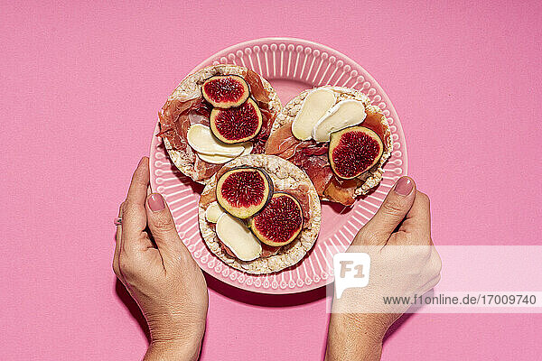 Hands of woman picking up plate with fresh rice cakes