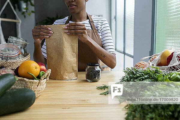 Frau mit Schürze in der Küche  beim Auspacken von frisch gekauftem Bio-Obst und -Gemüse Frau mit Schürze in der Küche, beim Auspacken von frisch gekauftem Bio-Obst und -Gemüse