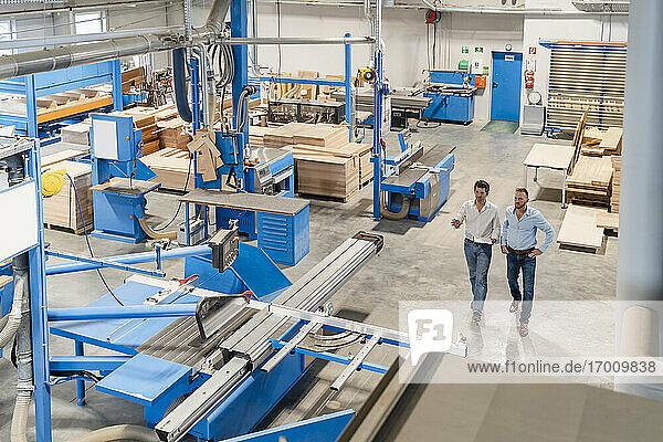 Zwei Zimmerleute gehen und unterhalten sich in einer Produktionshalle