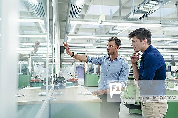Männliche Kollegen schauen durch ein Glas  während sie in einer Fabrik diskutieren