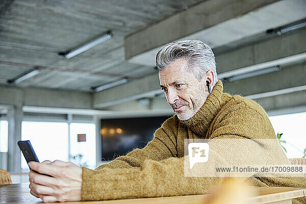 Mature man with in-ear headphones using mobile phone while sitting at office
