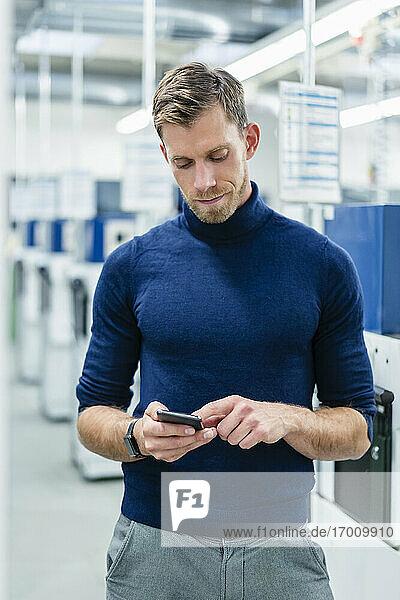 Gut aussehender Geschäftsmann  der ein Mobiltelefon in der Industrie benutzt