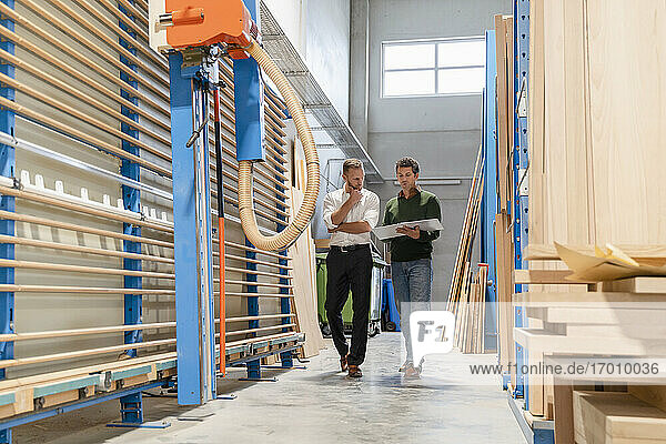 Two carpenters walking and talking amid wooden planks in production hall