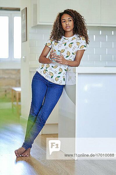 Afro junge Frau mit Kaffeetasse nachdenklich  während lehnt auf Küchentheke zu Hause Afro junge Frau mit Kaffeetasse nachdenklich, während lehnt auf Küchentheke zu Hause