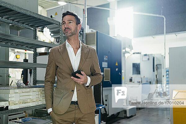 Lächelnder Geschäftsmann mit Händen in den Taschen  der ein Mobiltelefon hält und in die Ferne schaut