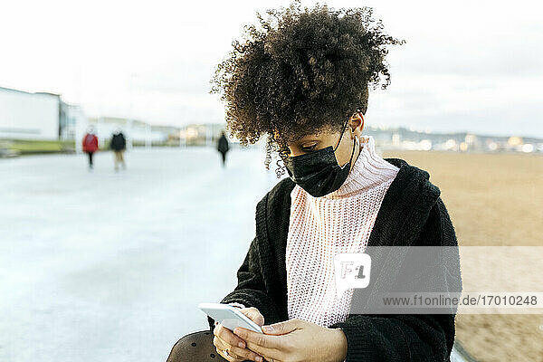 Woman with curly hair wearing face mask using smart phone while sitting against clear sky
