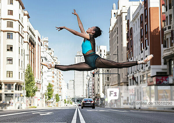 Ballet dancer dancing on road in city