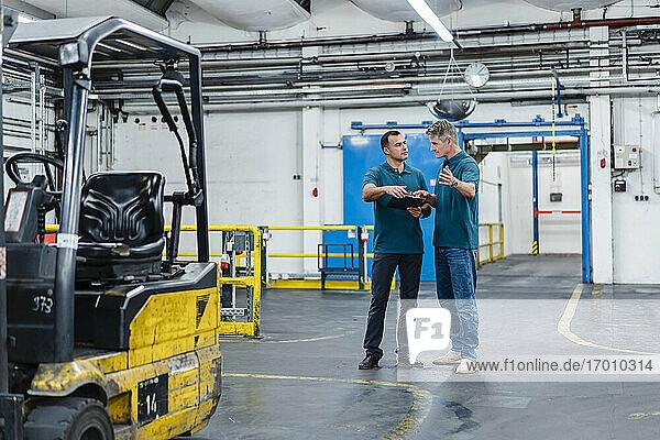 Männliche Berufsingenieure  die während ihrer Arbeit in der Industrie kommunizieren