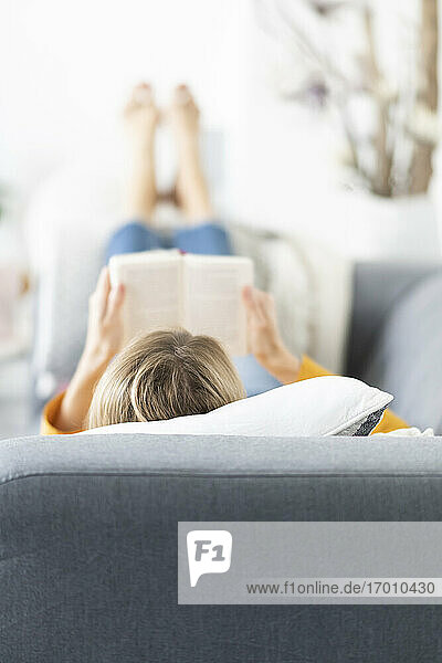 Blond woman reading book while relaxing on sofa at home