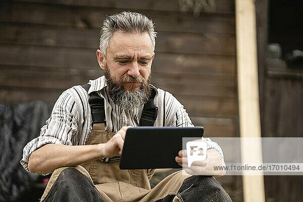 Porträt eines Zimmermanns  der in der Pause ein digitales Tablet benutzt Porträt eines Zimmermanns, der in der Pause ein digitales Tablet benutzt