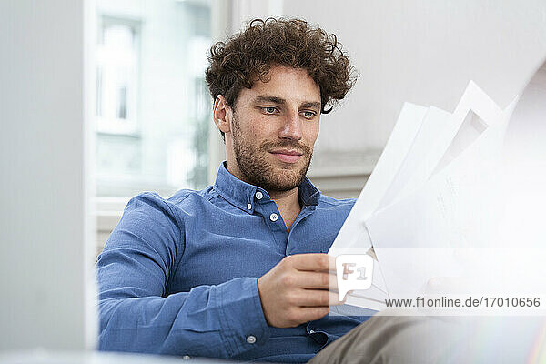 Male professional brainstorming while looking at paper document in office
