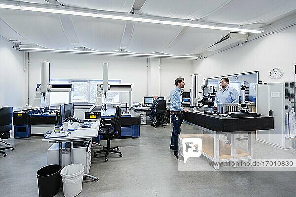 Ingenieure im Gespräch  während sie im Messraum im Büro stehen