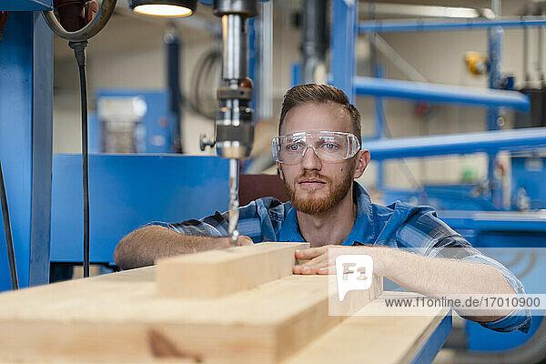 Porträt eines Zimmermanns mit Schutzbrille beim Bohren von Holzbrettern