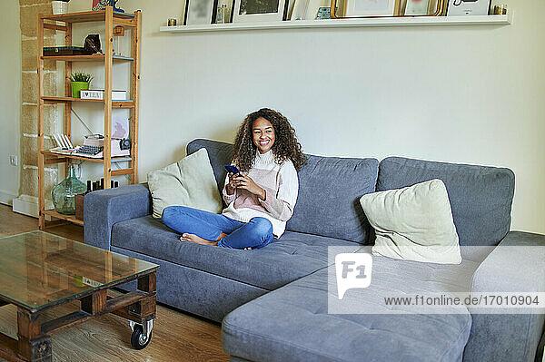 Lächelnde junge Frau  die nachdenklich ist und ihr Handy zu Hause in der Hand hält Lächelnde junge Frau, die nachdenklich ist und ihr Handy zu Hause in der Hand hält
