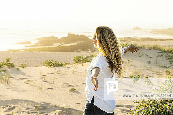 Carefree woman with arms outstretched standing on sand