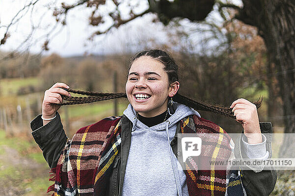 Braided smiling teenage girl in Autumn landscape