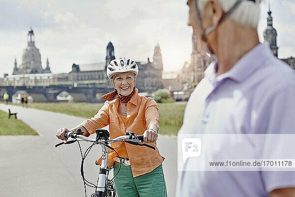 Lächelnde Frau mit Elektrofahrrad  die einen Mann ansieht  während sie an der Frauenkirche Dresden steht  Deutschland Lächelnde Frau mit Elektrofahrrad, die einen Mann ansieht, während sie an der Frauenkirche Dresden steht, Deutschland