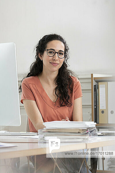 Female professional smiling while sitting at desk in office