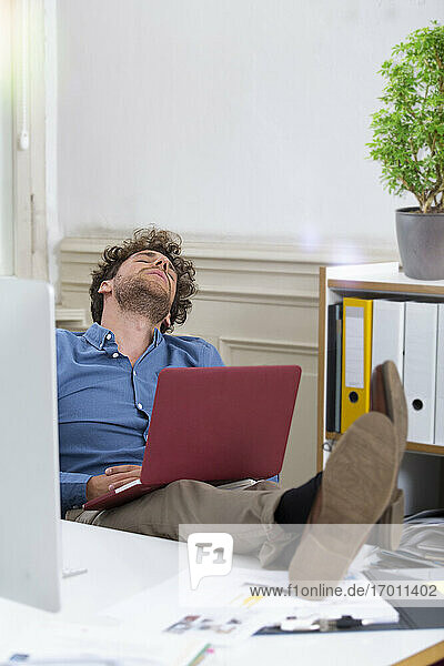 Male entrepreneur relaxing with laptop in office