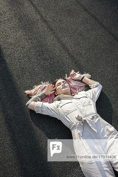 Hipster junge Frau mit geschlossenen Augen liegend auf dem Sportplatz Hipster junge Frau mit geschlossenen Augen liegend auf dem Sportplatz