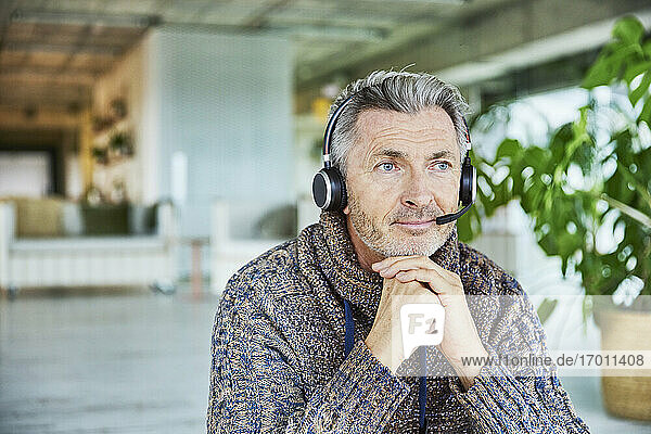 Businessman wearing headset sitting with hand on chin at office