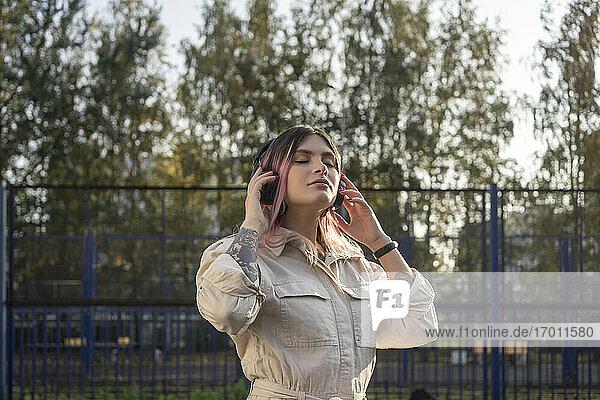 Modische Frau mit geschlossenen Augen hört Musik über Kopfhörer auf einem Sportplatz Modische Frau mit geschlossenen Augen hört Musik über Kopfhörer auf einem Sportplatz