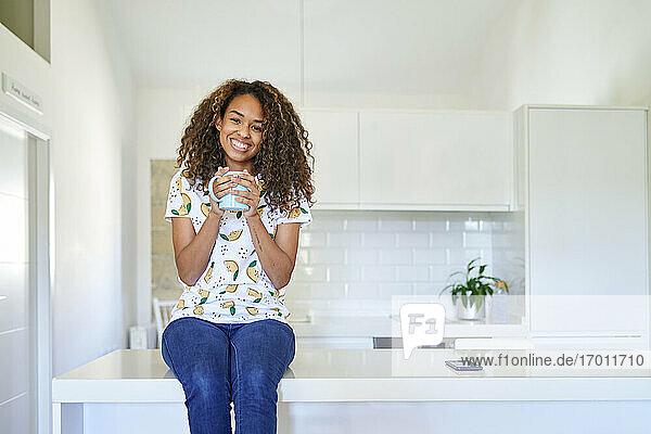 Lächelnde junge Frau mit Kaffeetasse auf dem Küchentisch zu Hause Lächelnde junge Frau mit Kaffeetasse auf dem Küchentisch zu Hause