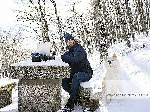 Cheerful photographer with laptop looking away while sitting on bench by akita dog on snow
