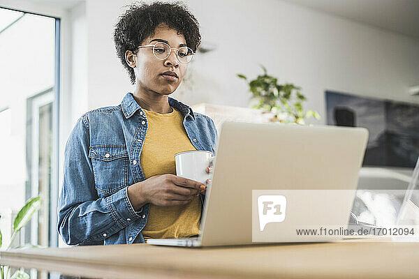 Frau hält Kaffeetasse und schaut auf Laptop zu Hause Frau hält Kaffeetasse und schaut auf Laptop zu Hause
