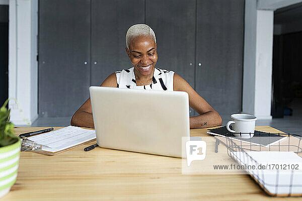 Geschäftsfrau  die in einem modernen Büro arbeitet und einen Laptop benutzt Geschäftsfrau, die in einem modernen Büro arbeitet und einen Laptop benutzt
