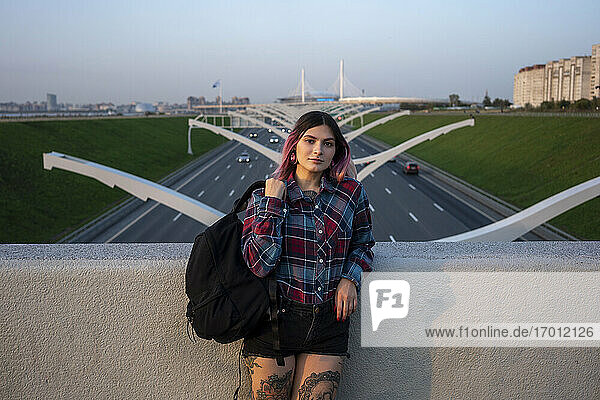 Hipster female with back pack leaning on retaining wall at bridge