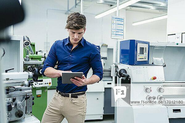 Männlicher Fachmann  der ein digitales Tablet an einer Produktionsanlage in einer Fabrik benutzt