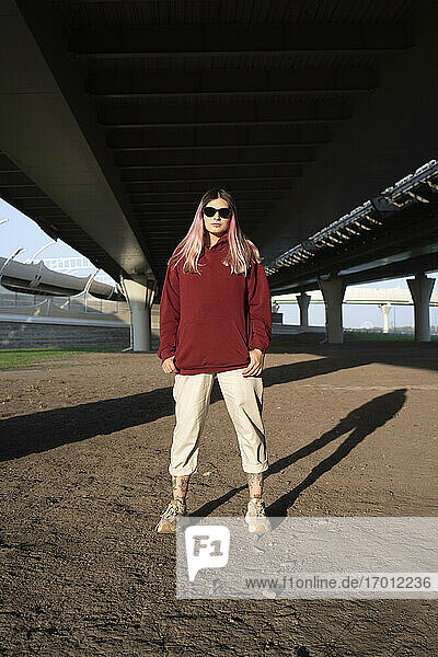 Modische junge Frau mit Sonnenbrille unter der Brücke an einem sonnigen Tag Modische junge Frau mit Sonnenbrille unter der Brücke an einem sonnigen Tag