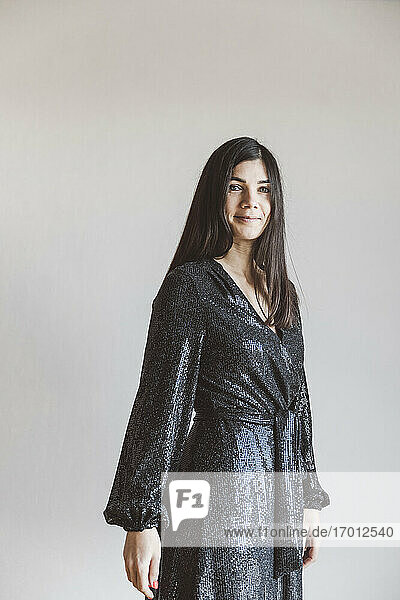 Beautiful mid adult woman wearing glittering dress smiling while standing at home