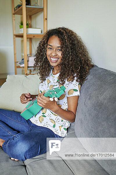 Lächelnde junge Afro-Frau mit Ukulele auf dem Sofa im Wohnzimmer sitzend Lächelnde junge Afro-Frau mit Ukulele auf dem Sofa im Wohnzimmer sitzend