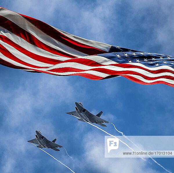Amerikanische Flagge weht im Wind und Lockheed Martin F-22 Raptors fliegen gegen den Himmel