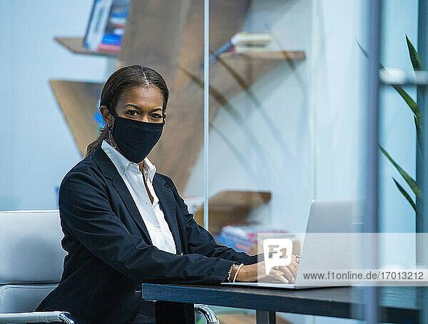 Porträt der Geschäftsfrau mit Gesichtsmaske arbeitet am Laptop am Schreibtisch im Büro