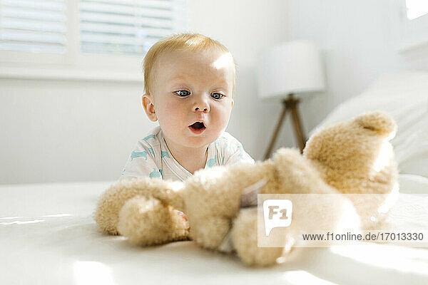 Baby-Junge (6-11 Monate) schaut auf Teddybär auf dem Bett
