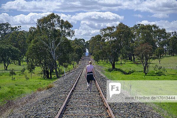 Australien  New South Whales  Frau wandert entlang der Bahnstrecke