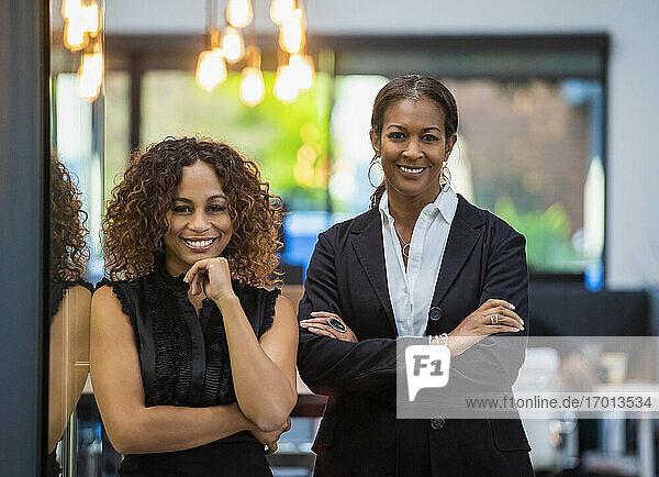 Porträt von zwei lächelnden Geschäftsfrauen im Büro stehend
