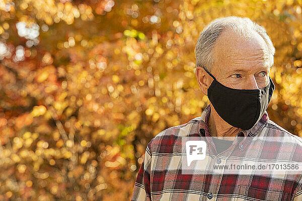 Porträt eines älteren Mannes mit Covid-Schutzmaske im Freien im Herbst