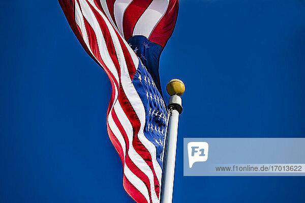 Amerikanische Flagge weht im Wind gegen blauen Himmel