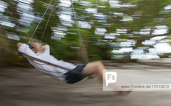 Älterer Mann schaukelnd am tropischen Strand  unscharfe Bewegung