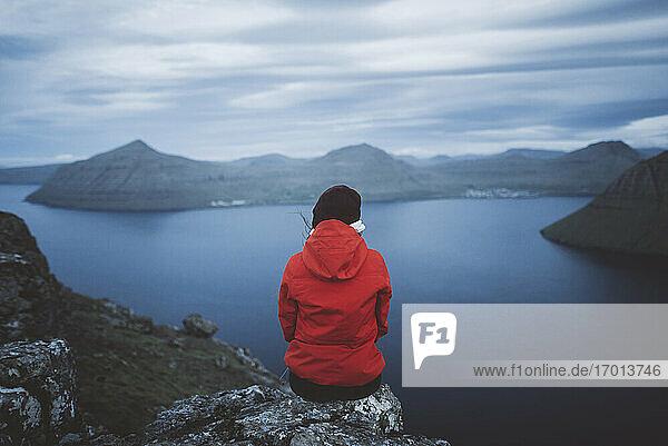 Dänemark  Färöer Inseln  Klaksvik  Frau sitzt am Rande einer Klippe über dem Meer und schaut auf die Aussicht