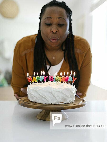 Frau bläst Kerzen auf Geburtstagskuchen aus