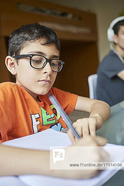 Zwei Jungen (8-9  14-15) lernen am Schreibtisch zu Hause während der Covid-19-Sperre