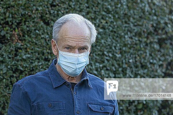 Porträt eines älteren Mannes im Freien  der im Herbst eine Schutzmaske aus Covid trägt